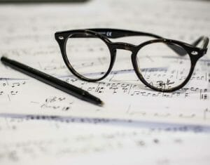 Glasses and pen on sheet music