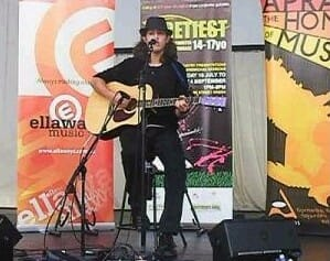 Tsoof singing and playing guitar at fRETfEST